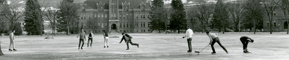 Archival photo of students playing hockey on the ice-covered oval.