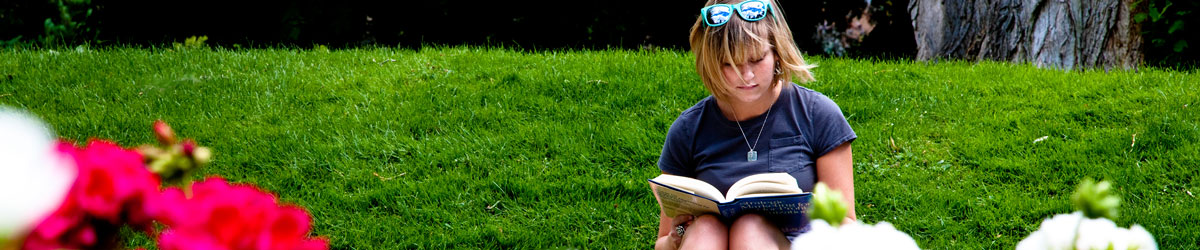 A student studies on a campus lawn.